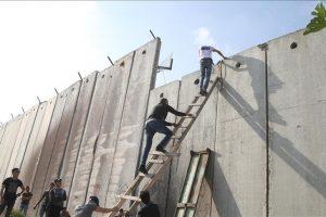 السلالم الخشبية وتسلق الجدار العازل وسيلة الفلسطينيين للوصول إلى المسجد الأقصى